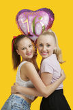 Un ritratto di due giovani donne felici con il pallone di compleanno che abbraccia sopra il fondo giallo Fotografia Stock