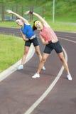 Un ritratto di due giovani sportive di Feale che hanno allungamento si esercita all'aperto Immagine Stock