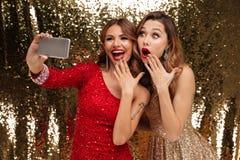 Un ritratto di due ha eccitato le donne allegre in vestiti frizzanti Immagine Stock