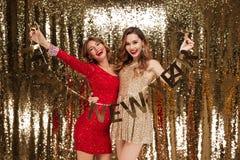 Un ritratto di due ha eccitato le donne attraenti in vestiti frizzanti Immagine Stock Libera da Diritti