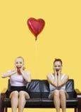 Un ritratto di due ha stupito le giovani donne che si siedono sul sofà con il pallone a forma di cuore sopra fondo giallo Immagine Stock