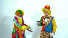 Un ritratto di due pagliacci divertenti che giocano con le pentole ed i falso-dolci stock footage