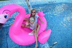 Un ritratto di due ragazze che indossano gli occhiali da sole, amici felici sul galleggiante gonfiabile di nuotata del fenicotter fotografia stock