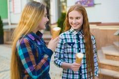 Un ritratto di due ragazze dell'adolescente che stanno insieme mangianti il gelato Fotografia Stock