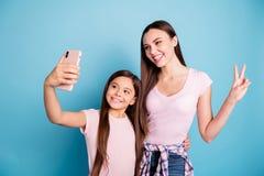Un ritratto di due ragazze diritto-dai capelli di buon umore allegre adorabili attraenti affascinanti sveglie piacevoli che posan fotografia stock libera da diritti