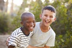 Un ritratto di due ragazzi che abbracciano e che ridono duri all'aperto fotografia stock