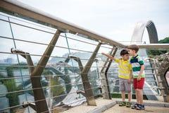 Un ritratto di due ragazzi scherza una passeggiata sopra un ponte e lo sguardo giù, bambino che cammina fuori nel giorno soleggia immagini stock