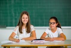 Un ritratto di due scolare in un'aula Fotografie Stock Libere da Diritti