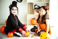 Un ritratto di due sorelle felici nel costume di Halloween che divide t immagini stock