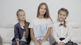 Un ritratto di due sorelline felici che stringono a sé tenero seduta sullo strato comodo in salone accogliente e tre ragazze stock footage