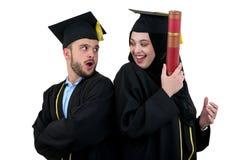 Un ritratto di due studenti musulmani arabi di laurea felici Isolato sopra fondo bianco Fotografia Stock