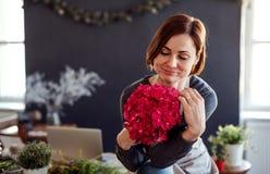 Un ritratto di giovane donna creativa in un negozio di fiore Una partenza dell'affare del fiorista fotografia stock