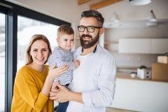 Un ritratto di giovane famiglia con una ragazza del bambino che si muove nella nuova casa fotografie stock libere da diritti