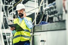 Un ritratto di un ingegnere industriale dell'uomo con lo smartphone in una fabbrica, lavorante fotografia stock libera da diritti