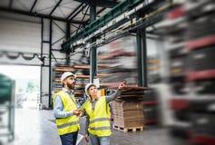 Un ritratto di un ingegnere industriale della donna e dell'uomo con la compressa in una fabbrica, lavorante fotografie stock