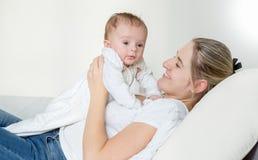 Un ritratto di 3 mesi del neonato che si trova sulla madre sorridente sul letto Fotografie Stock Libere da Diritti