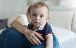 Un ritratto di 10 mesi del neonato che striscia sopra la madre che si trova a letto e che guarda in camera Immagine Stock Libera da Diritti