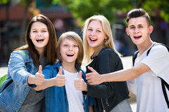 Un ritratto di quattro adolescenti che stanno e che tengono sfoglia su togeth fotografia stock libera da diritti