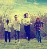 Un ritratto di quattro amici che corrono sul campo Fotografia Stock Libera da Diritti