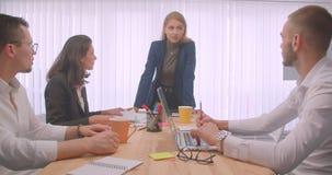 Un ritratto di quattro collleagues allegri che celebrano e che danno su cinque sul posto di lavoro all'interno Dire della donna d archivi video