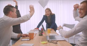 Un ritratto di quattro collleagues allegri che celebrano e che gettano le carte nell'ufficio all'interno Dire della donna di affa stock footage