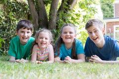 Un ritratto di quattro fratelli e sorelle che si trovano nel giardino a casa fotografie stock