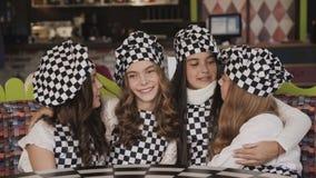 Un ritratto di quattro ragazze divertenti esamina la macchina fotografica negli abbracci in pizzeria 4K video d archivio