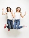 Un ritratto di stile di vita di due giovani migliori amici delle ragazze dei pantaloni a vita bassa salta Fotografia Stock Libera da Diritti