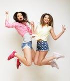 Un ritratto di stile di vita di due giovani migliori amici delle ragazze dei pantaloni a vita bassa salta Fotografie Stock Libere da Diritti
