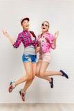 Un ritratto di stile di vita di due giovani migliori amici delle ragazze dei pantaloni a vita bassa salta in studio Immagine Stock