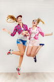 Un ritratto di stile di vita di due giovani migliori amici delle ragazze dei pantaloni a vita bassa salta in studio Fotografia Stock