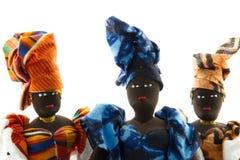 Un ritratto di tre bambole africane che indossano gli involucri della testa Fotografia Stock