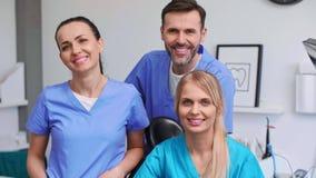 Un ritratto di tre, dentisti sorridenti nella clinica del dentista video d archivio
