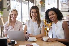 Un ritratto di tre donne di affari che si incontrano nella caffetteria immagini stock