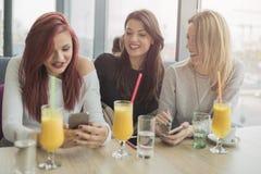 Un ritratto di tre giovani belle donne che per mezzo del telefono cellulare al co Fotografie Stock