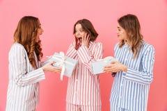 Un ritratto di tre ragazze sveglie caucasiche 20s che indossano stri variopinto Fotografia Stock Libera da Diritti
