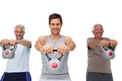 Un ritratto di tre uomini che si esercitano con le campane del bollitore Fotografie Stock Libere da Diritti