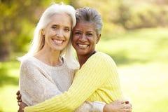 Un ritratto di un abbracciare femminile maturo di due amici Fotografia Stock
