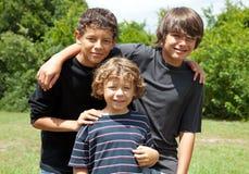 Un ritratto di un sorridere di tre ragazzi Immagine Stock