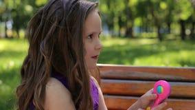Un ritratto di una bambina sveglia di cinque anni su un banco in un parco di estate stock footage