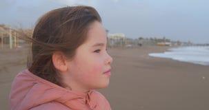 Un ritratto di una condizione della ragazza sulla spiaggia nell'orario invernale archivi video