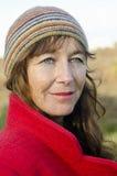 Un ritratto di una donna nei suoi gli anni quaranta che portano un colore rosso Fotografia Stock