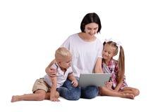 Un ritratto di una famiglia felice isolata su un fondo bianco Una madre sorridente con i suoi bambini che tengono un computer por Fotografie Stock Libere da Diritti