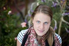 Un ritratto di una giovane donna che che cerca nella macchina fotografica con un fondo verde del giardino della lavanda Immagine Stock