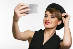 Un ritratto di una giovane signora molto attraente che fa selfie in uno studio della foto Fotografia Stock Libera da Diritti