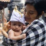 Un ritratto di una madre con il suo bambino che è 3 mesi nelle armi della madre I bambini posano facendo uso delle fasce tipiche  immagine stock libera da diritti