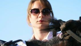 Un ritratto di una ragazza della puleggia tenditrice, tiene le redini nel suo guanto di cuoio, afferra un cavallo per una crinier video d archivio