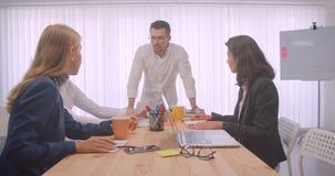 Un ritratto di una riunione allegra di quattro collleagues sul posto di lavoro all'interno Uomo d'affari che cammina dentro e che stock footage