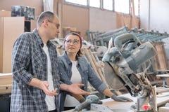 Un ritratto industriale di due lavoratori e della donna, parlante alle macchine utensili fotografia stock