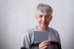 Un ritratto orizzontale dell'uomo maturo attraente con capelli e le grinze grigi si è vestito in maglione casuale che tiene una c Immagine Stock